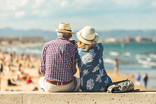 Older couple sitting at the seaside enjoying the view of happy families and bright sunshine