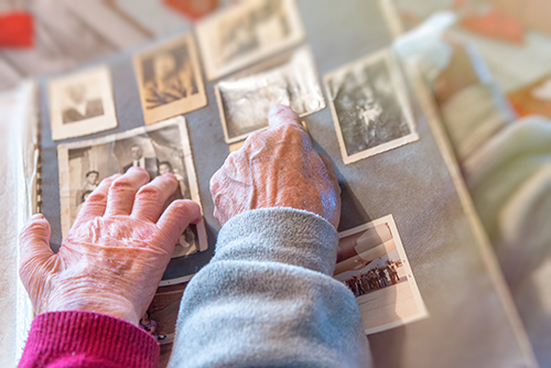 Older couple looking though a photo album cherishing the memories of their loved ones and friends