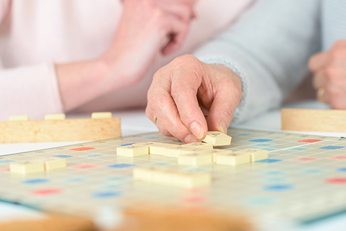 Older couple playing a game of scrabble and appreciating their time spent together